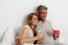 Glückliches Paar, das auf dem Bett frühstückt Lizenzfreies Stockbild