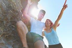 Glückliches Paar, das auf dem Felsen weg zeigt steht stockfoto