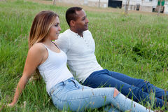 Glückliches Paar, das auf dem Gras auf dem Gebiet liegt Stockfotografie