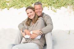 Glückliches Paar, das auf dem Sand sitzt Stockbild