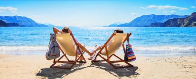 Glückliches Paar, das auf dem Strand sich entspannt lizenzfreies stockbild