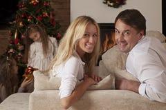 Glückliches Paar, das auf der Couch mit Weihnachtsbaum sitzt Stockfotografie