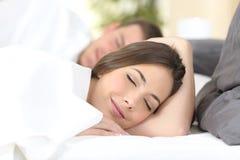 Glückliches Paar, das auf einem Bett schläft Lizenzfreies Stockfoto