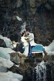 Glückliches Paar, das auf Felsen auf dem Hintergrund der Natur umarmt Stockfotografie