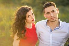 Glückliches Paar, das auf Gras im Park stillsteht Stockbild
