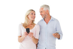 Glückliches Paar, das auf ihren Smartphones simst Lizenzfreie Stockbilder