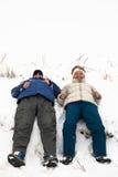 Glückliches Paar, das auf Schnee stillsteht Stockbilder