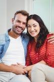 Glückliches Paar, das auf Sofa In Living Room sitzt lizenzfreie stockfotos