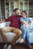 Glückliches Paar, das auf Sofa In Living Room sitzt lizenzfreie stockfotografie