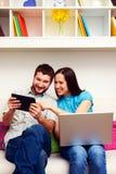 Glückliches Paar, das auf Sofa sitzt Stockfotografie