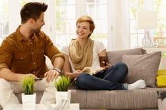 Glückliches Paar, das auf Sofa stillsteht stockfotos