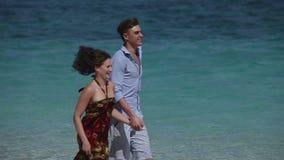 Glückliches Paar, das auf tropischem Strand läuft stock video footage