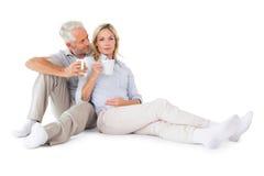 Glückliches Paar, das Becher halten sitzt Lizenzfreie Stockfotos