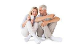 Glückliches Paar, das Becher halten sitzt Stockfotografie