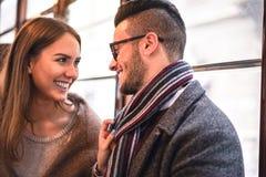 Glückliches Paar, das beim Schauen im Bus - junge Schönheit zieht ihren Freund durch Schal nahe bei ihr lacht stockbild