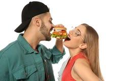 Glückliches Paar, das den Burger lokalisiert isst stockfoto