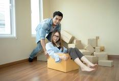 Glückliches Paar, das den jungen Mann des Spaßes drückt die junge Frau sitzt O hat stockfoto