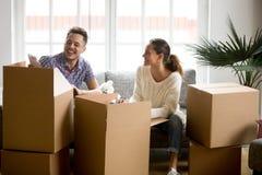 Glückliches Paar, das den Spaß lacht hat, Kästen an beweglichem Tag auspackend stockbild