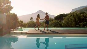 Glückliches Paar, das in den Swimmingpool im Freien springt stock video footage