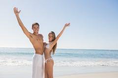 Glückliches Paar, das an der Kamera und am Wellenartig bewegen lächelt Lizenzfreie Stockbilder