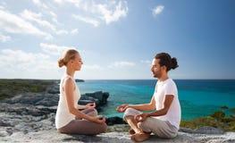 Glückliches Paar, das in der Lotoshaltung auf Strand meditiert Stockfotos