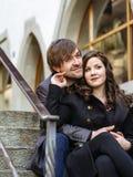 Glückliches Paar, das in der Stadt sitzt und stillsteht Stockfotografie