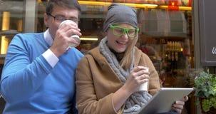 Glückliches Paar, das Digital-Tablet am Straßen-Café verwendet stock footage