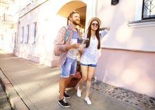 Glückliches Paar, das draußen besichtigend geht und Karte halten Stockfotografie
