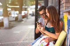 Glückliches Paar, das draußen in einem Café- und Uhrtelefon sitzt Lizenzfreies Stockfoto