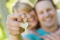 Glückliches Paar, das draußen leeren Haus-Schlüssel hält Lizenzfreie Stockbilder