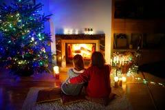 Glückliches Paar, das durch einen Kamin in einem gemütlichen Wohnzimmer auf Weihnachtsabend legt Stockfotografie