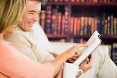 Glückliches Paar, das ein Buch in einem Lesesaal liest und coffe trinkt lizenzfreie stockbilder