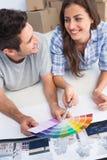 Glückliches Paar, das ein Farbdiagramm betrachtet, um ihr Haus zu verzieren Stockbilder