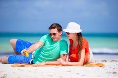 Glückliches Paar, das ein Foto auf einem Strand an den Feiertagen macht Stockbild