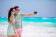 Glückliches Paar, das ein Foto auf weißem Strand an den Flitterwochenfeiertagen macht Stockfotografie