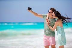Glückliches Paar, das ein Foto auf weißem Strand an den Flitterwochenfeiertagen macht Stockfotos