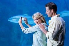 Glückliches Paar, das ein Foto von Fischen macht Lizenzfreie Stockbilder