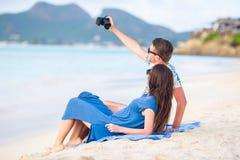 Glückliches Paar, das ein selfie Foto auf weißem Strand macht Zwei Erwachsene, die ihre Ferien auf tropischem exotischem Strand g Stockfotos
