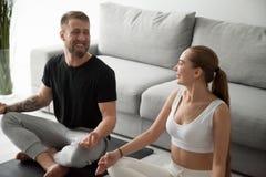 Glückliches Paar, das einander beim zu Hause meditieren betrachtet stockfotografie