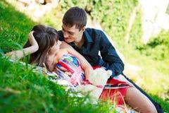 Glückliches Paar, das in einem sonnigen Sommerpark flirtet Stockbilder