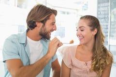 Glückliches Paar, das einiges Kuchen genießt Lizenzfreie Stockfotografie