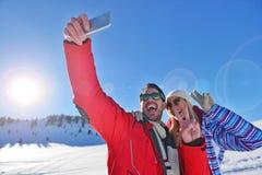 Glückliches Paar, das Foto mit Smartphone selfie Stock an über Winterhintergrund macht Lizenzfreie Stockbilder