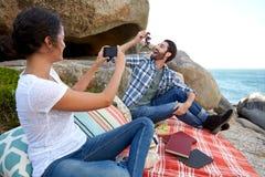 Glückliches Paar, das Fotos während eines entspannten Picknicks auf dem Felsen macht Lizenzfreies Stockbild