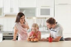 Glückliches Paar, das frisch ihre Tochter mit Ofen gebackenem Brötchen behandelt stockfoto