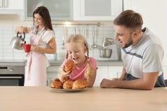 Glückliches Paar, das frisch ihre Tochter mit Ofen gebackenem Brötchen behandelt lizenzfreie stockfotos