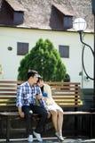 Glückliches Paar, das am Gartenstuhl sitzt Stockbild