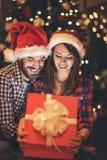 Glückliches Paar, das Geschenk im Kasten Sylvesterabenden betrachtet lizenzfreies stockbild