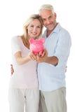 Glückliches Paar, das ihr Sparschwein zeigt Lizenzfreie Stockfotos