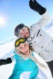 Glückliches Paar, das ihre Feiertage in den schneebedeckten Bergen genießt Stockfoto