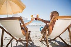 Glückliches Paar, das ihre Gläser bei der Entspannung auf ihrer Plattform klirrt Lizenzfreie Stockfotos